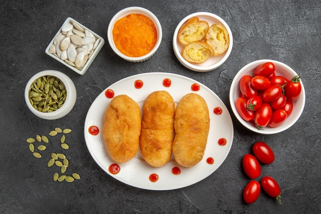 Bovenaanzicht aardappel hotcakes met verse kleine tomaten op donkergrijze achtergrond taart bak oven hotcake cake