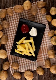 Bovenaanzicht aardappel met ketchup en mayo op houten achtergrond