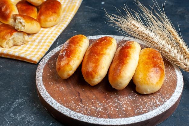 Bovenaanzicht aardappel piroshki op keukenhanddoek en houten bord tarwe op tafel kopie ruimte