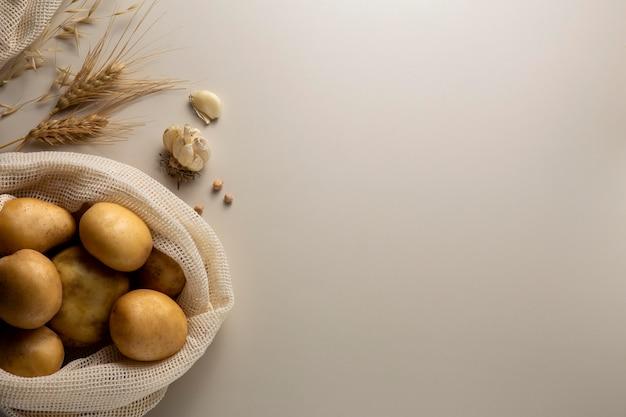 Bovenaanzicht aardappelen en knoflook met kopieerruimte