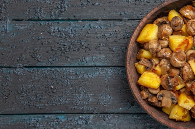 Bovenaanzicht aardappelen met champignons bruine kom met aardappelen en champignons aan de rechterkant van de tafel