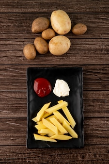 Bovenaanzicht aardappelen met ketchup en mayo op houten achtergrond