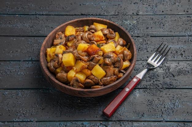 Bovenaanzicht aardappelen met paddenstoelenbord met aardappelen en champignons en een vork in het midden van de grijze tafel