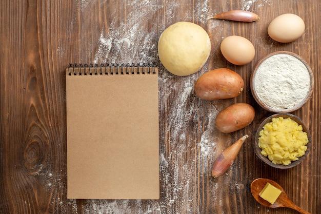 Bovenaanzicht aardappelpuree met bloem en aardappelen op bruin houten bureau, pittige peper, rijp aardappelvoedsel