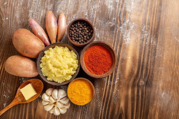 Bovenaanzicht aardappelpuree met verse aardappelen en kruiden op houten bureau maaltijd ingrediënt kleur deeg bakken