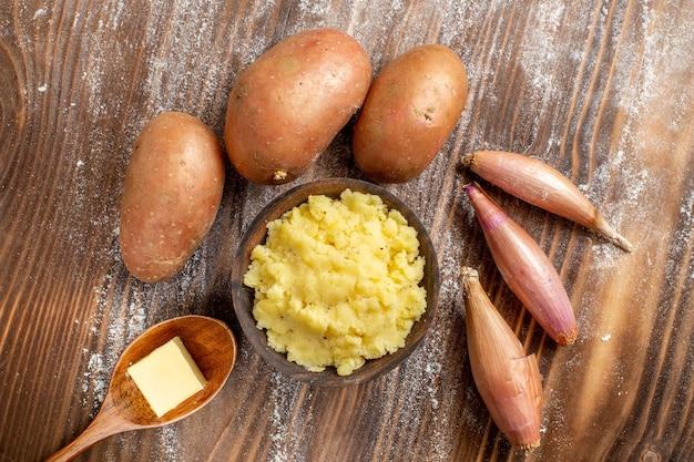 Bovenaanzicht aardappelpuree met verse aardappelen op houten bureau maaltijd ingrediënt kleur deeg bakken
