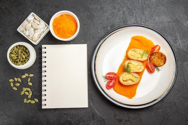 Bovenaanzicht aardappeltaarten met gepureerde pompoen en zijn zaden op donkergrijze achtergrond bak oven taart kleur taart