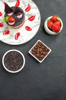 Bovenaanzicht aardbei cheesecake op witte ovale bord kommen met aardbeien chocolade koffie zaden op donkere ondergrond