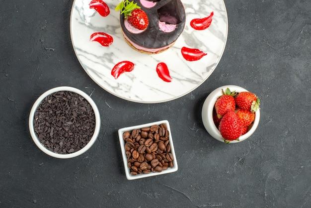 Bovenaanzicht aardbei cheesecake op witte ovale bord kommen met aardbeien en chocolade op donkere ondergrond