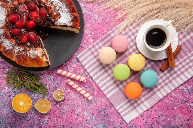 Bovenaanzicht aardbei chocoladetaart met kopje thee en macarons op roze bureau