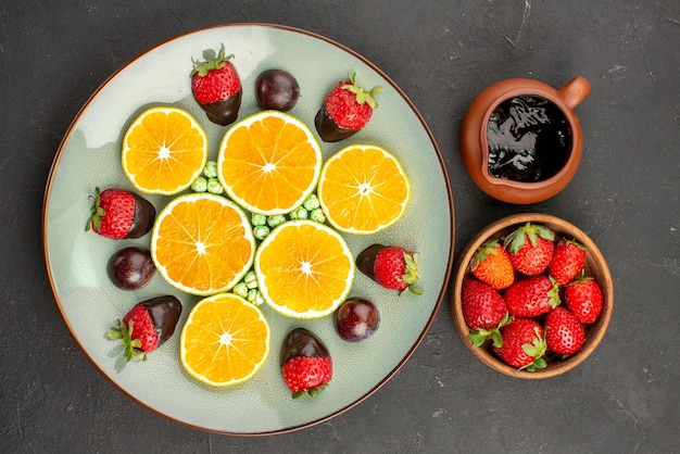 Bovenaanzicht aardbei en chocolade smakelijke chocoladesaus en aardbeien en groene snoepjes met chocolade bedekte aardbei gehakte sinaasappel op witte plaat op tafel