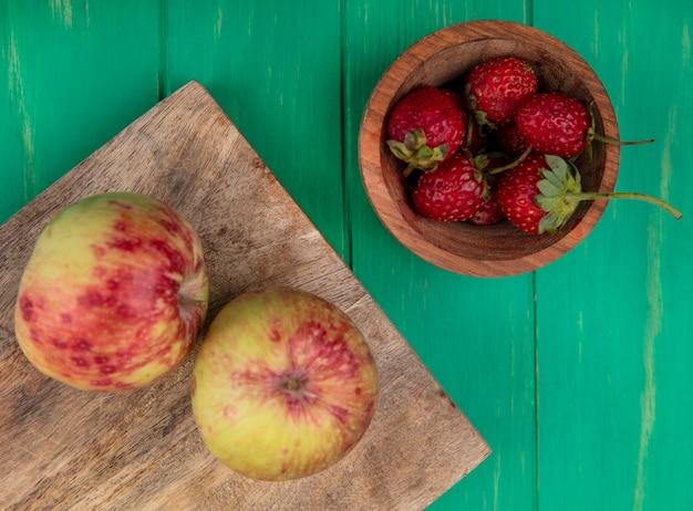 Bovenaanzicht aardbei in kom met appels op snijplank