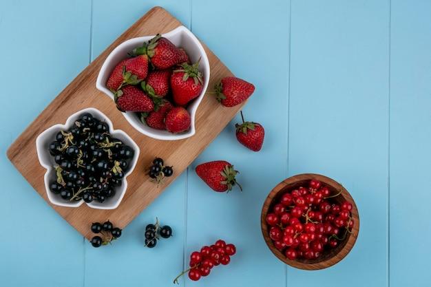 Bovenaanzicht aardbei met zwarte bessen op een bord met rode aalbessen in een kom op een blauwe achtergrond