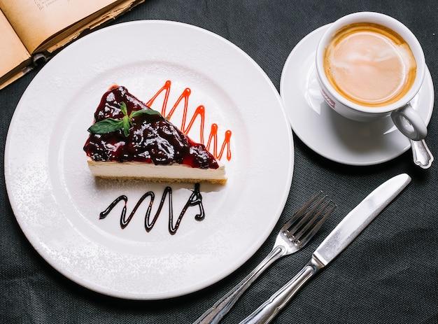 Bovenaanzicht aardbeien cheesecake met een kopje cappuccino