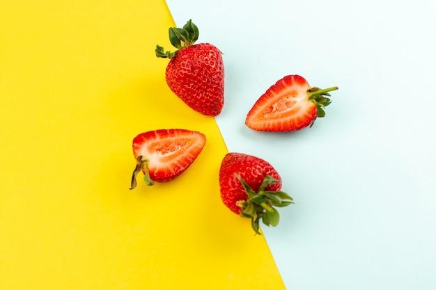 Bovenaanzicht aardbeien gesneden hele sappige mellow op het geel blauwe bureau
