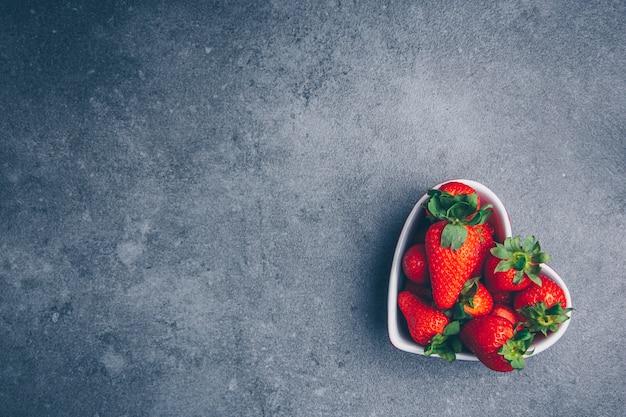 Bovenaanzicht aardbeien in hartvormige kom op grijze gestructureerde achtergrond. horizontale vrije ruimte voor uw tekst