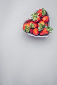 Bovenaanzicht aardbeien in hartvormige kom op witte achtergrond. verticale vrije ruimte voor uw tekst