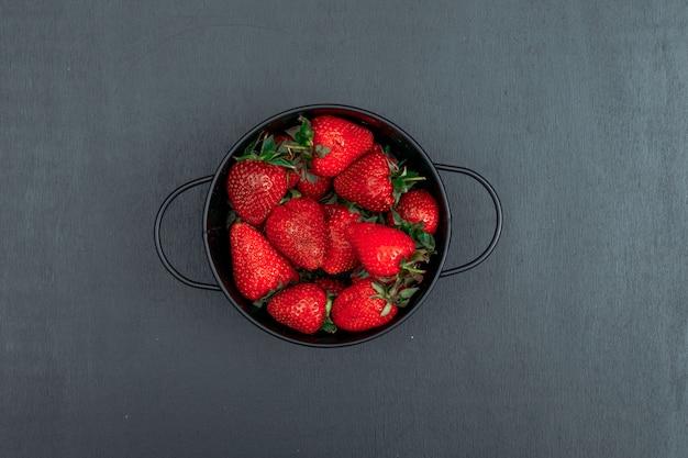 Bovenaanzicht aardbeien in ijzeren kom op zwarte achtergrond. horizontaal