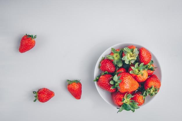 Bovenaanzicht aardbeien in kom op witte achtergrond. horizontaal