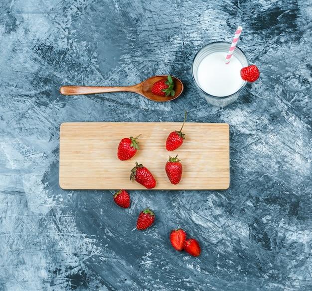 Bovenaanzicht aardbeien op snijplank met melk en een houten lepel op donkerblauw marmeren oppervlak. horizontaal