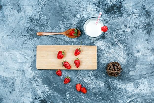 Bovenaanzicht aardbeien op snijplank met melk, schoothoek en een houten lepel op donkerblauw marmeren oppervlak. horizontaal
