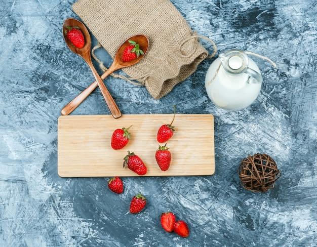 Bovenaanzicht aardbeien op snijplank met melk, schoothoek, houten lepels en een stuk zak op donkerblauw marmeren oppervlak. horizontaal