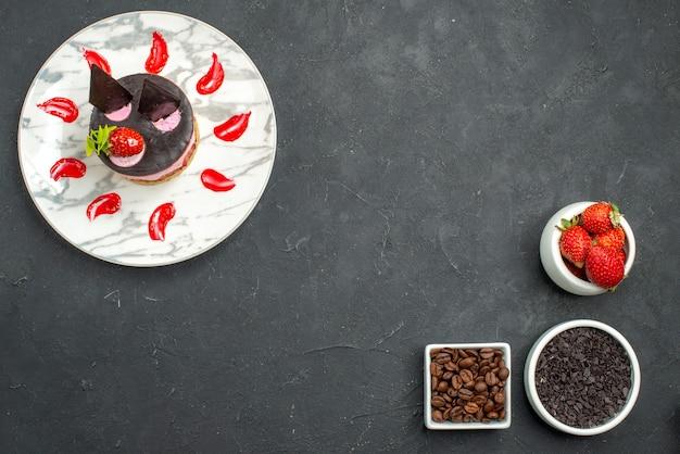 Bovenaanzicht aardbeiencheesecake op witte ovale plaat linksboven en kommen met aardbeienchocoladekoffiezaden rechtsonder op donkere ondergrond