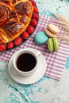 Bovenaanzicht aardbeientaart met franse macarons en thee op blauwe ondergrond