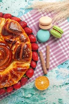 Bovenaanzicht aardbeientaart met franse macarons op blauwe ondergrond