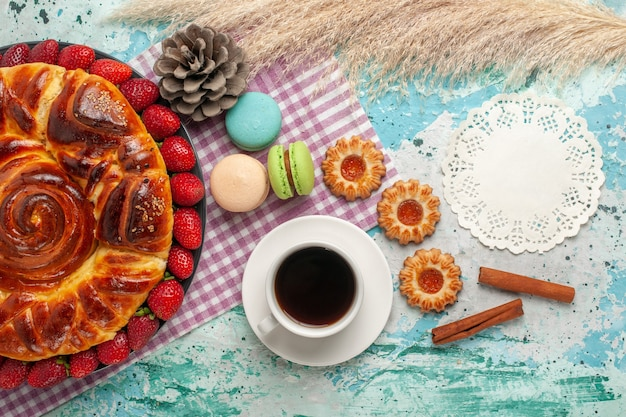 Bovenaanzicht aardbeientaart met koekjes franse macarons en kopje thee op blauwe ondergrond