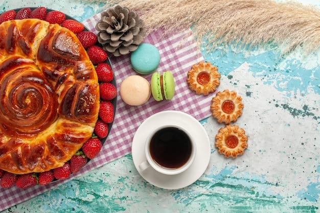 Bovenaanzicht aardbeientaart met koekjes macarons en kopje thee op blauwe ondergrond