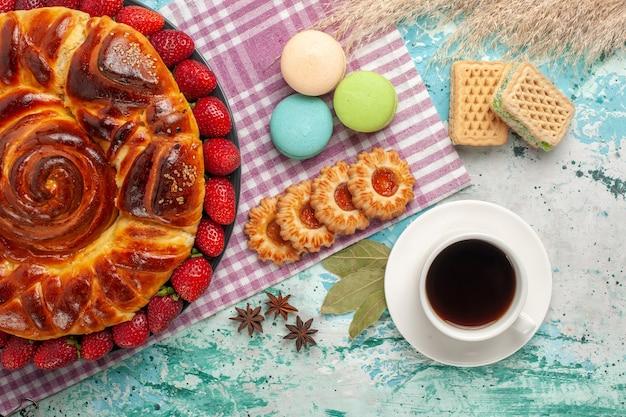 Bovenaanzicht aardbeientaart met kopje thee en franse macarons op blauwe ondergrond