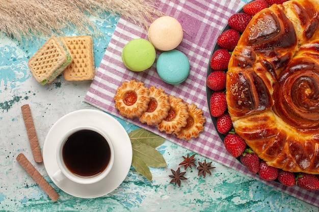 Bovenaanzicht aardbeientaart met kopje thee koekjes en franse macarons op blauwe ondergrond