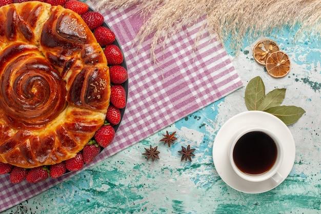 Bovenaanzicht aardbeientaart met kopje thee op het blauwe oppervlak