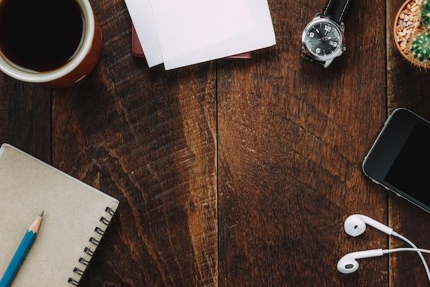 Bovenaanzicht accessoires bureau de mobiele telefoon, tag, potlood, notitiepapier, koffie, cactus, koptelefoon op houten kantoor bureau achtergrond.