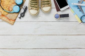 Bovenaanzicht accessoires om te reizen concept.White mobiele telefoon en koptelefoon op houten achtergrond.