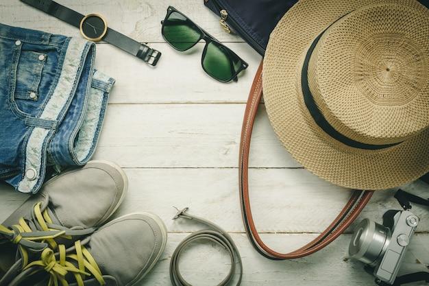 Bovenaanzicht accessoires om te reizen met vrouwen kleding concept.belt, tas, hoed, camera, ketting, broek, horloge en zonnebril op witte houten tafel background.file lay, mode woman.copy ruimte.