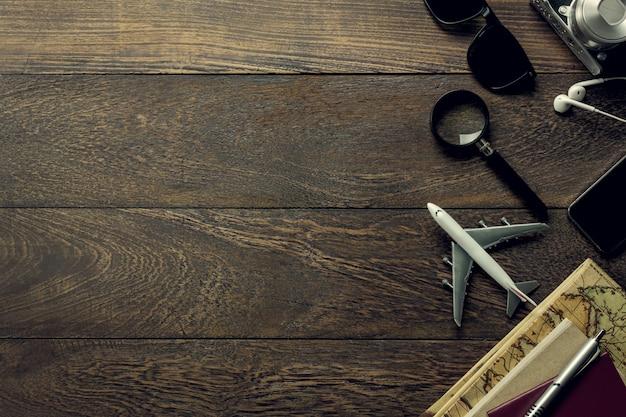Bovenaanzicht accessoires reizen met mobiele telefoon, paspoort, camera, oortelefoon, notitieblok, zonnebril, kaart, vergrootglas op tafel houten met kopie ruimte. reis concept.