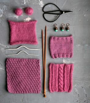 Bovenaanzicht: accessoires voor breien en monsters van gebreide producten liggen op een grijze betonnen achtergrond. plaats voor inschrijving.