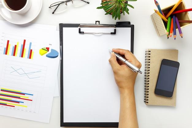 Bovenaanzicht accessoires zakelijk bureau met zakenman.businessman werken met papierwerk, mobiele telefoon, koffie, notitieboekje, cactus, klembord op wit bureau met kopie ruimte.