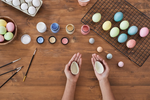 Bovenaanzicht achtergrond van kinderhanden die pastelkleurige paaseieren schilderen over houten tafel, doe-het-zelf paasdecoraties, kopieer ruimte