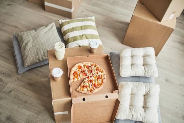 Bovenaanzicht achtergrondafbeelding van pizza op kartonnen doos als geïmproviseerde tafel in lege kamer terwijl familiemo...