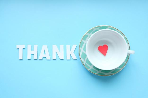 Bovenaanzicht afbeelding beker met zin: dank, volgende en kleine rode hart.