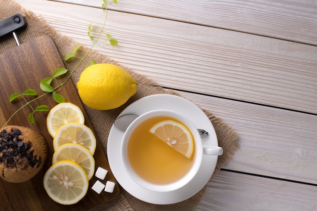 Bovenaanzicht afbeelding van een kopje thee met citroen op houten tafel