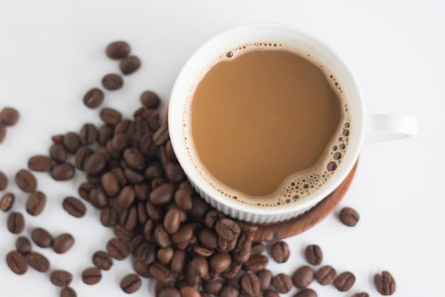 Bovenaanzicht afbeelding van koffiebonen en witte kop geïsoleerd op een witte achtergrond.