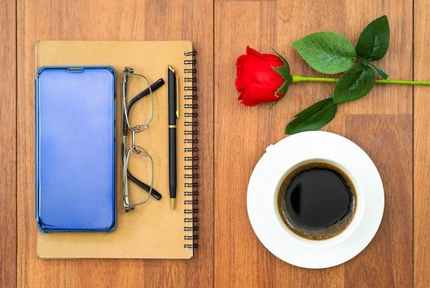 Bovenaanzicht afbeelding van koffiekopje, notebook en mobiel met oogglas op houten tafel achtergrond voor het toevoegen van tekst of mockup