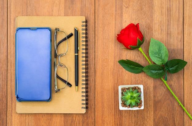 Bovenaanzicht afbeelding van notebook en mobiel met rode roos op houten tafel achtergrond