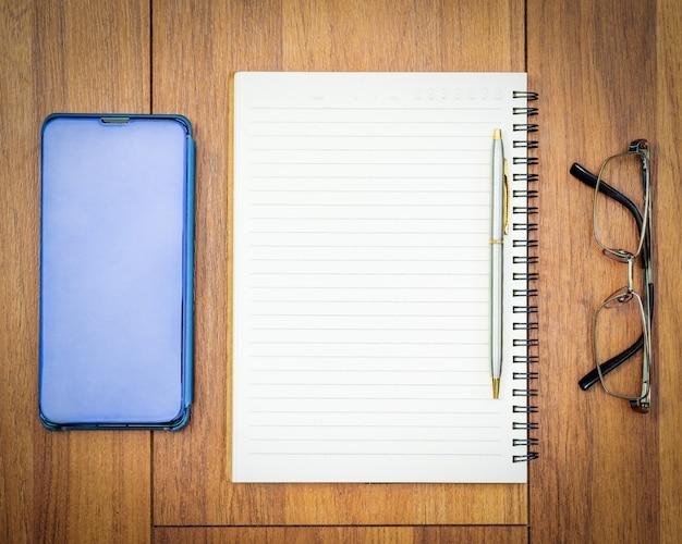 Bovenaanzicht afbeelding van notitieblok openen met blanco pagina en mobiel op houten tafel