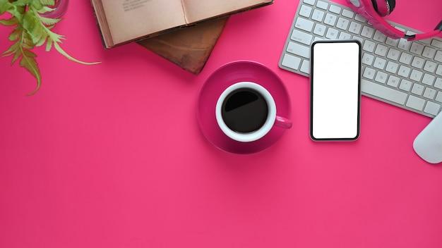 Bovenaanzicht afbeelding van roze bureau. draadloze koptelefoon, witte smartphone met leeg scherm, boeken, koffiekopje, potplant, draadloze muis en toetsenbord samen op een vrouwelijk bureau.