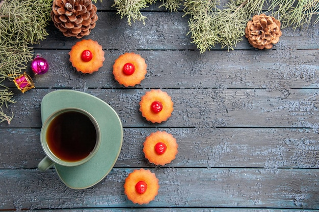 Bovenaanzicht afgerond kersen cupcakes fir-tree takken kerst speelgoed kegels en een kopje thee op donkere houten tafel met kopie ruimte